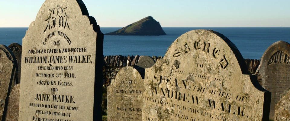 A view through old gravestones to the Mewstone in the bay