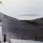 A second view down the valley from the Lodge. The ladies are standing outside the main door on the north side of the house.Their dresses suggest a late 19th or early 20th century date. The Plymouth breakwater, completed many years before in1841,can again be seen in the Sound.