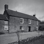 Knighton Farmhouse in the mid-1980s. Owned in the early 1950s by Ben Clifton, in 1953 it was bought by Henry (later Sir Henry) Studholme when the Cliftons moved to Eggbuckland. Henry Studholme put in a farm manager, Mr Stevenson, who remained there until the late 1980s. The picture shows the farmhouse just before the end of Mr Stevenson's time as tenant. Peter Lugar recalls the farm had a specially constructed sheep dip, to which other farmers brought their animals. When this was first used the headmistress of the school, Mrs Algate, was asked to calculate the dilution of the chemical to ensure there were no dire consequences!