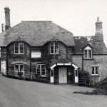 The Jubilee Inn, now the Odd Wheel, as it was in the late 1940s, and in reality little different to its appearance in 1900. The pub provided a focus in the eastern part of the parish, and for several decades in the mid-twentieth century was run by members of the Perring family. The left hand edge of the roof shows signs of repair due to it being damaged by a cattle lorry attempting to get down to West Wembury Farm.  The road was very narrow until widening in 1958, as can be seen by the hedge on the extreme left of the photograph.