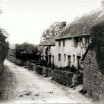 "West Wembury cottages in 1909. Like the Knighton Hill cottages, these were the rented homes of agricultural workers and their families. The left-hand pair are quite recognisable today, although they have had alterations such as changes to door positions and windows.  The right-hand pair have changed dramatically, having been rebuilt in 1910 in the Edwardian style. The changes included a raised roofline and the loss of the thatched roofs; alterations to the arrangement and style of the windows and doors; and the addition of chimneys on the gable ends.  Reflecting the rebuild's timing, the left-hand one of the pair is named ""Coronation Cottage"" in honour of King George V whose Coronation took place that year. Meanwhile the lane, constrained by the cottages on the right and the wall on the left, is exactly the same width as today."