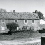West Wembury farmhouse and yard, 1980. The house is Grade II listed, and is a very substantial stone-built house of the 18th century, with a slate-hung front elevation, granite quoins, and 19th-century sash windows.  This was a working farm for much of the twentieth century, but in the 1960s and 70s its land was almost all developed as today's Wembury was built. At this point the farmstead fell into disuse – as can be seen from the weeds in the yard and the absence of farm implements and livestock. An equivalent picture of the working farm can be seen in this website's 'Langdon Estate in 1927' photo gallery.  The view is through the farmyard gateway, through which the cows were led twice daily to and from their pasture.  The gateway is now blocked off, and the growth of trees and shrubs has almost obscured the yard and farmhouse from view.